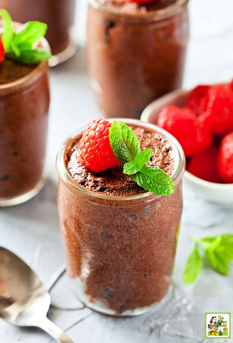 Glasses of Vegan Chocolate Mousse served with garnish of raspberries and mint.