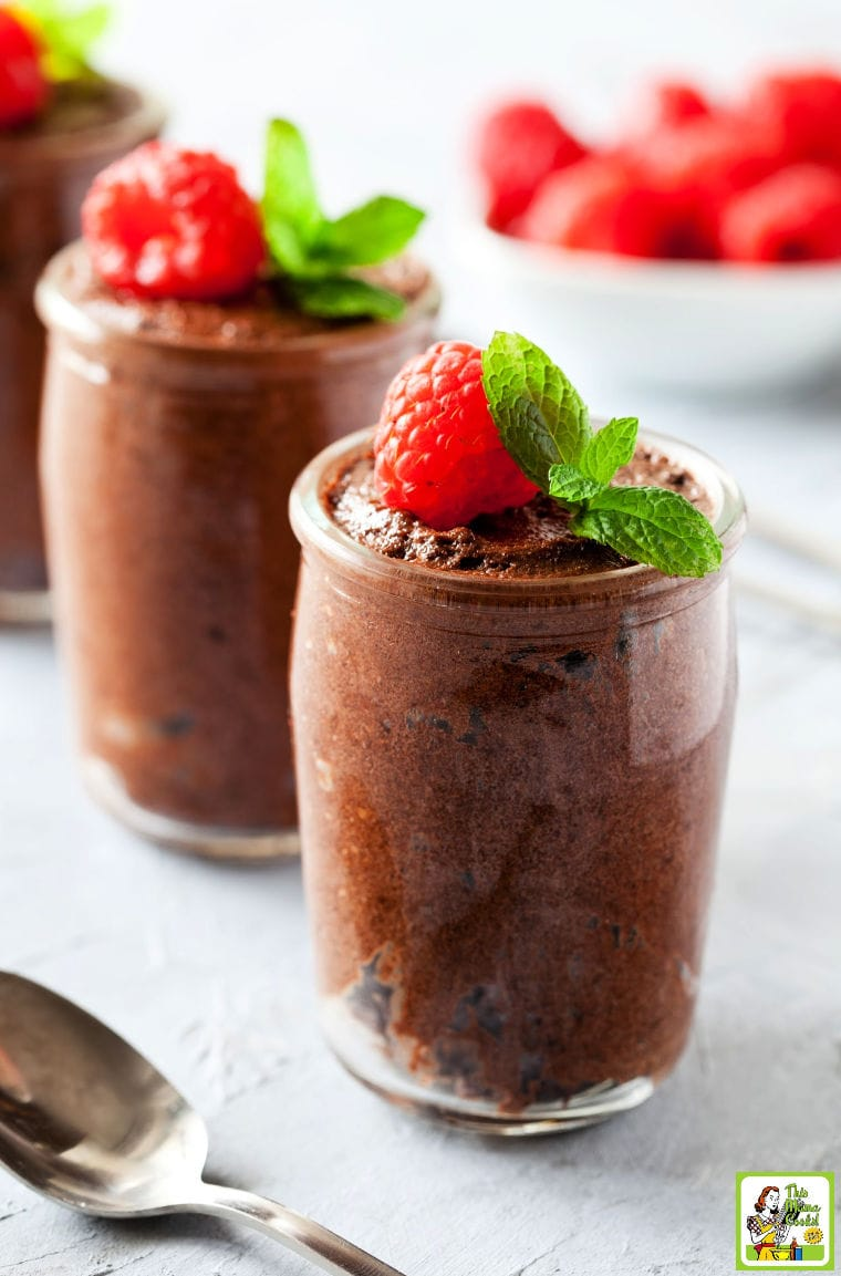 Two serving glasses of Vegan Chocolate Mousse made with tofu served with garnish of raspberries and mint. With a bowl of raspberries in the background and a spoon in the foreground.
