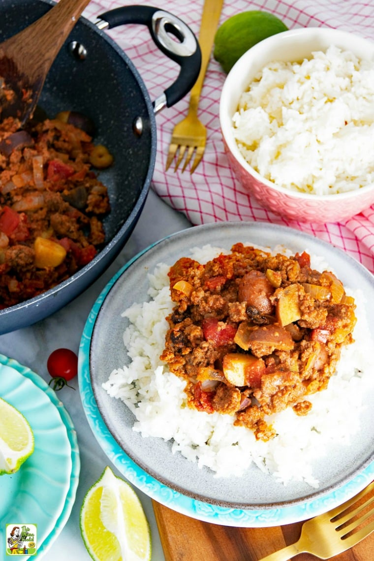 Mexican Picadillo served on rice, with bowl of rice, and picadillo in frying pan with wooden spoon.