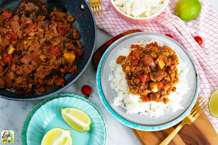 Mexican Picadillo served on ricewith picadillo in frying pan and sliced limes