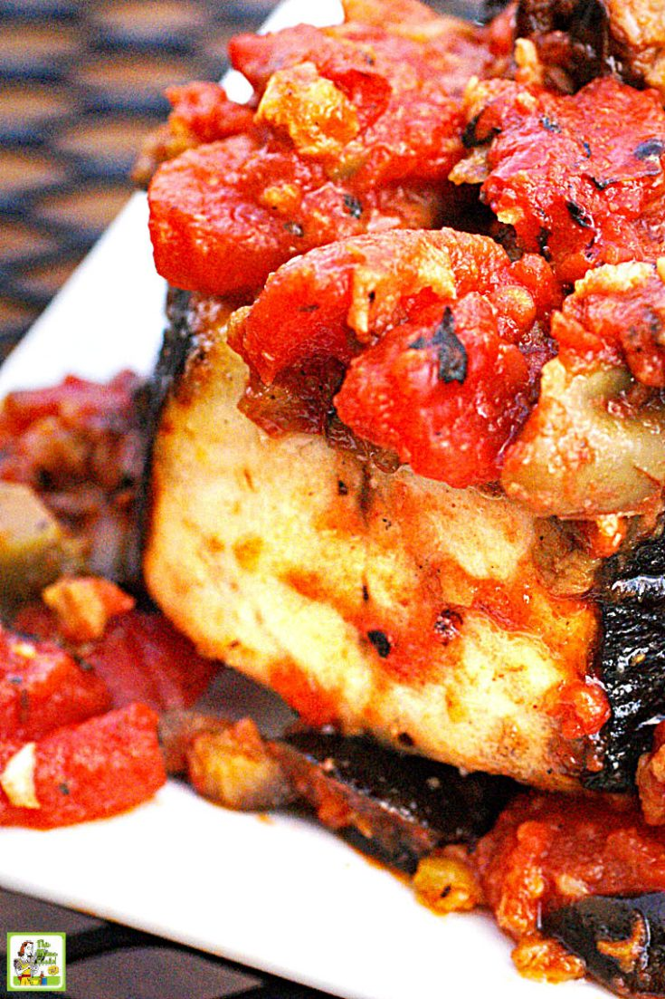 Closeup of a grilled wahoo steak with cooked tomatoes and olives on a white plate.