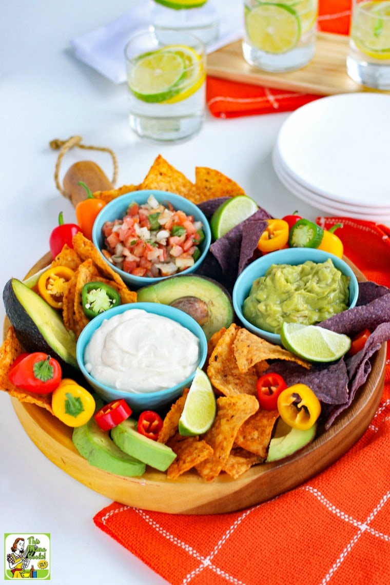 Overhead view of a platter with a small blue bowl of Vegan Sour Cream with slices of limes, tortilla chips, mini sweet peppers, avocados, blue bowls of salsa and guacamole, with white plates and glasses of water with slices of limes and lemon.