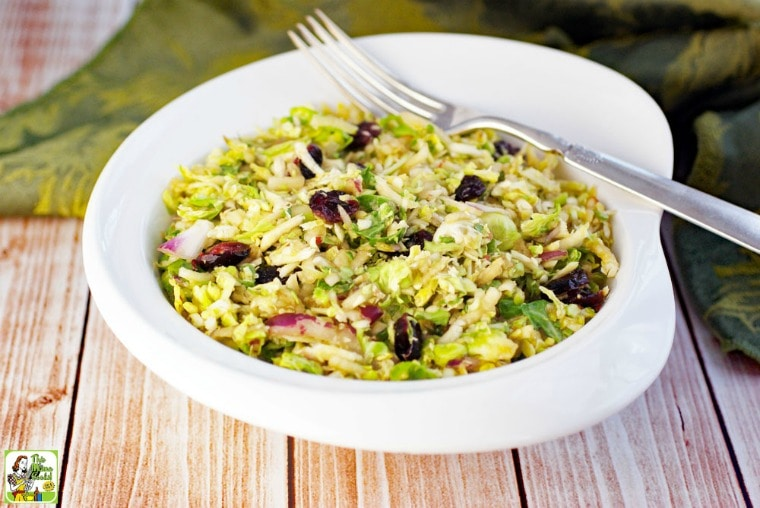 A white bowl of Brussel Sprouts Salad with Cranberries with fork and green napkin.