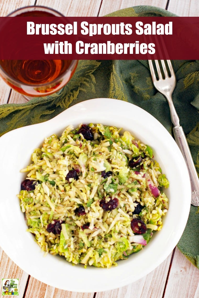 A bowl of brussel sprouts salad with cranberries with a glass of tea and a fork.
