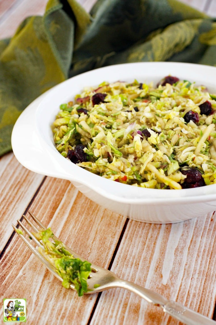 A white bowl of shredded brussel sprouts salad with cranberries, green napkin, and a fork.