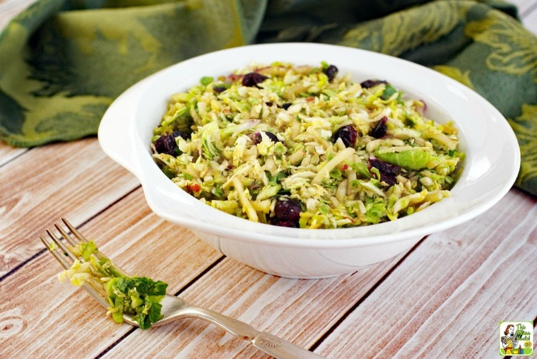 A white bowl of shredded brussel sprouts salad with cranberries with green napkins.