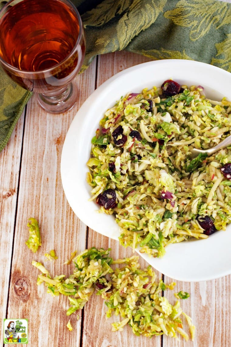 A white bowl of shredded brussel sprouts salad with cranberries with a glass of iced tea.