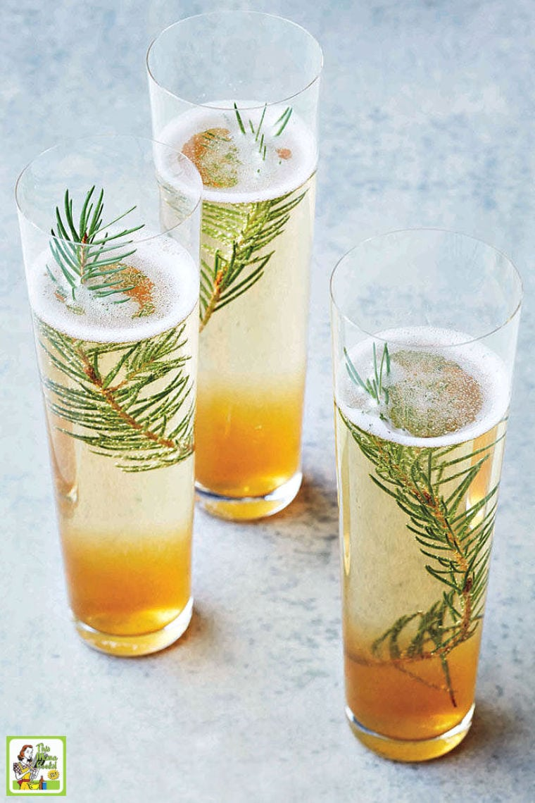 Three champagne cocktails in tall glasses served with pine sprigs.