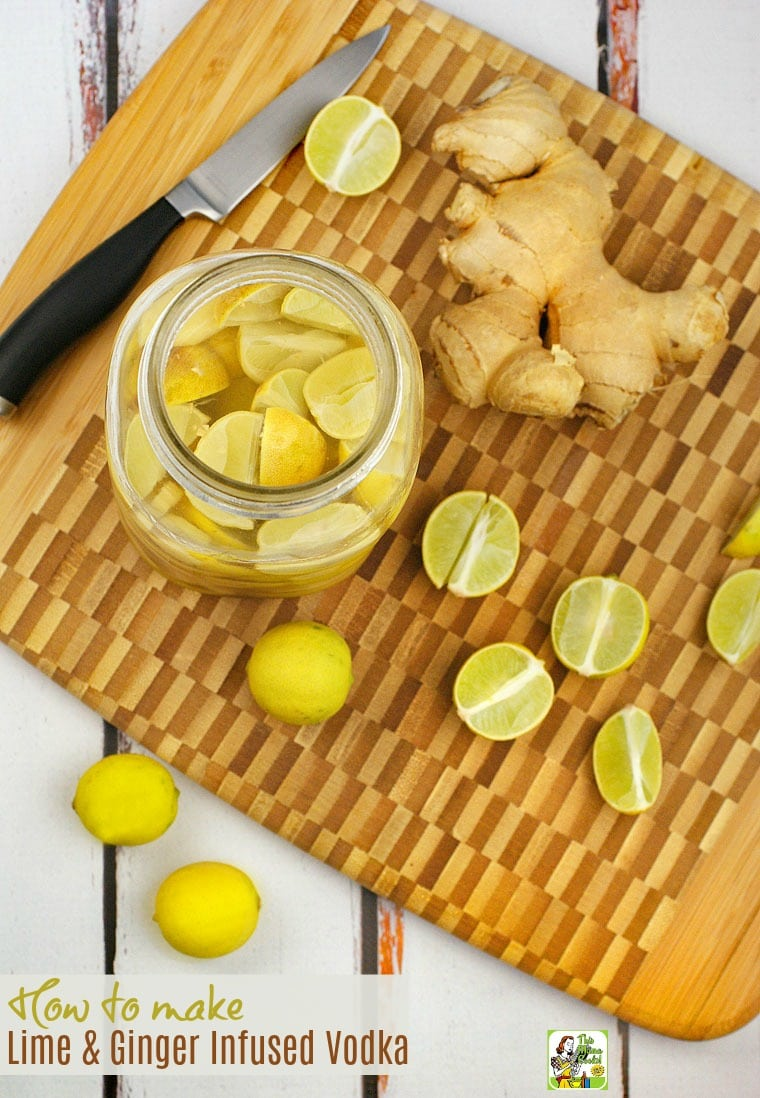 A mason jar of Lime & Ginger Infused Vodka on a wooden cutting board with limes and ginger and a knife.