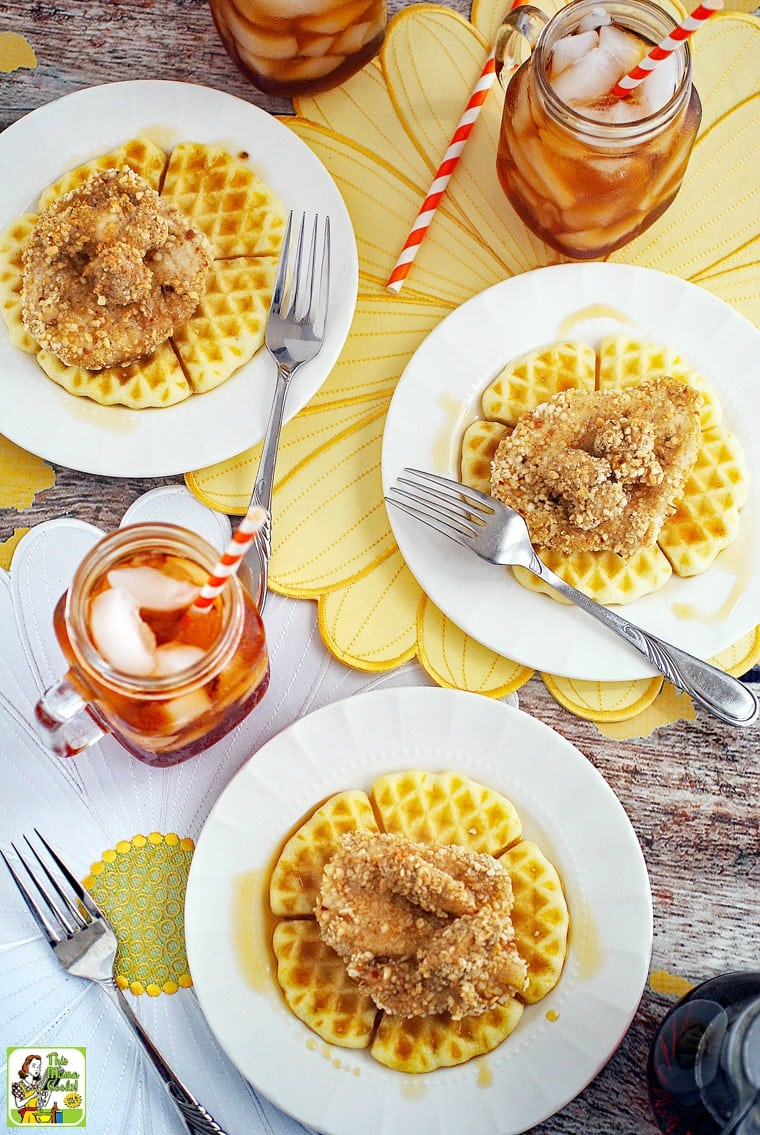 Overhead view of chicken and waffles covered on a white plates with forks, glasses of ice tea, and straws, on white and yellow floral placemats.