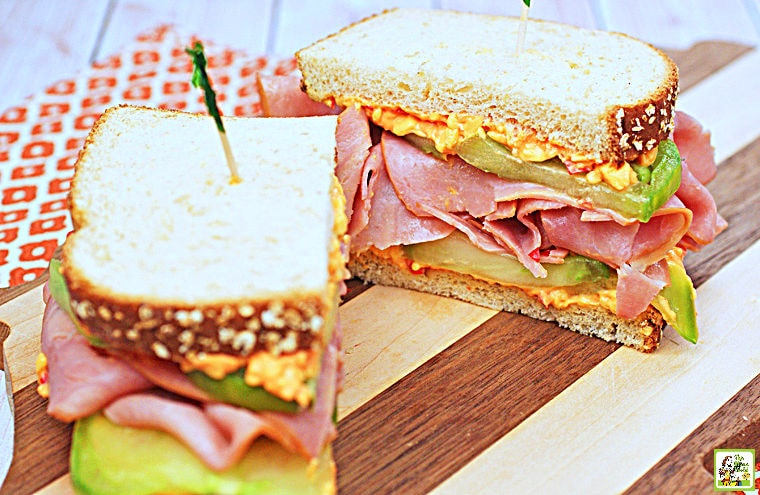 Ham & Pimento Cheese Sandwich cut in half on a wooden cutting board with an orange and white napkin.