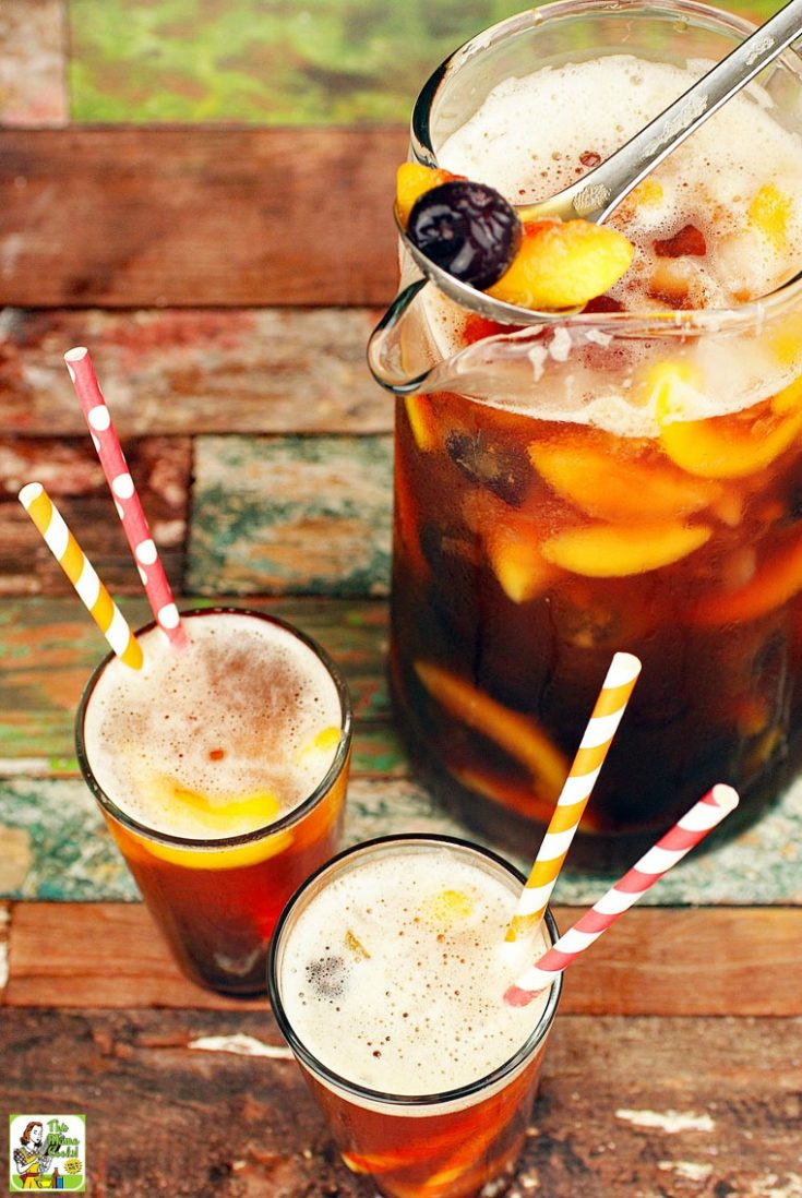 A pitcher and glasses with straws of iced tea with fruit.