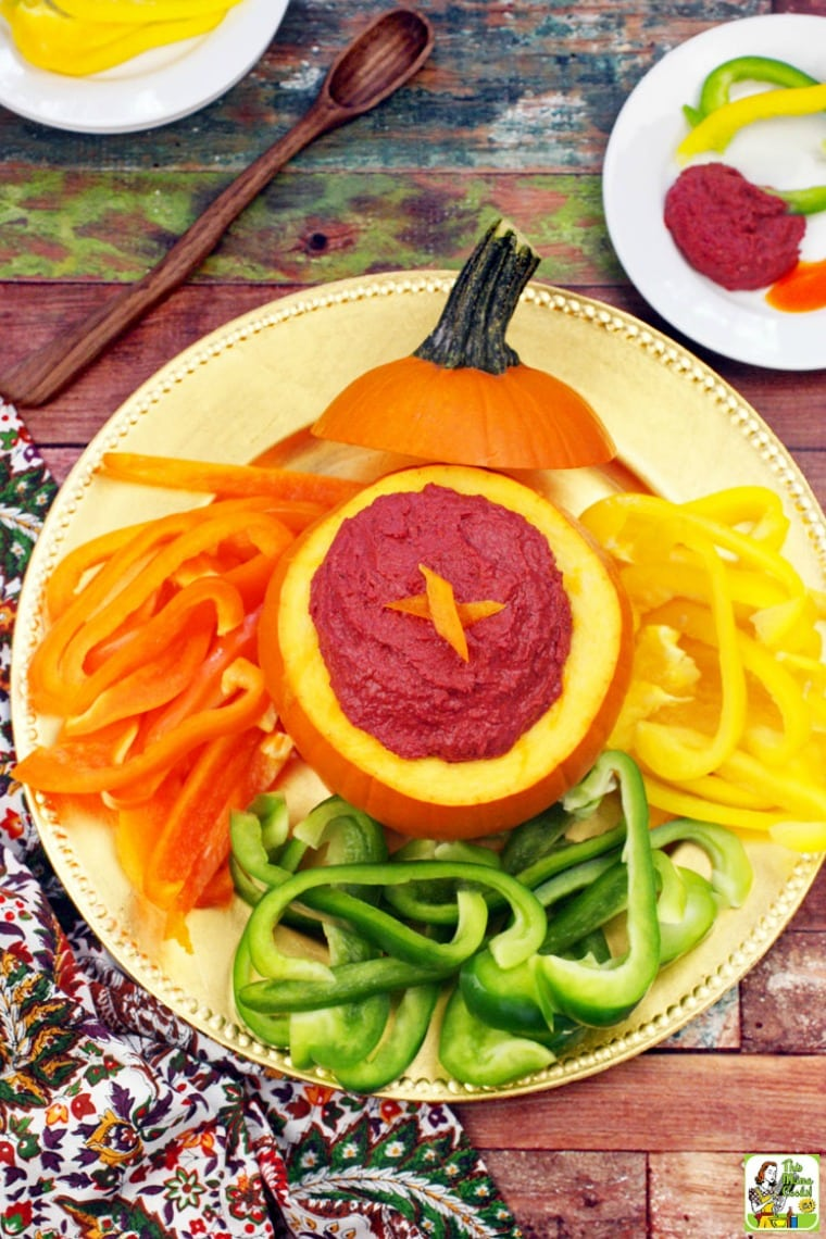 Spicy Hummus in a pumpkin with sliced peppers on a gold plate.