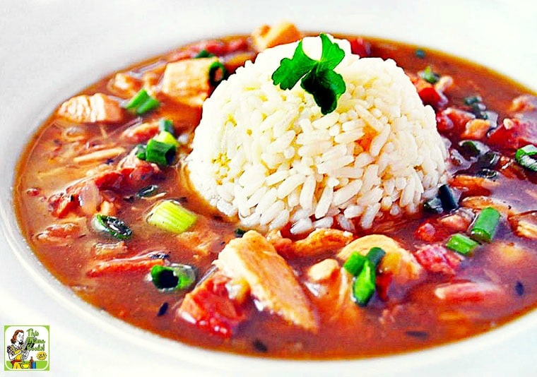 A bowl of Chicken and Sausage Gumbo with a scoop of rice in the middle.