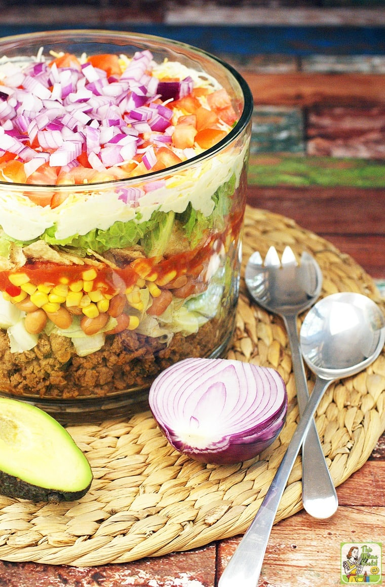 Taco salad in a trifle bowl with onion, avocado and serving utensils.