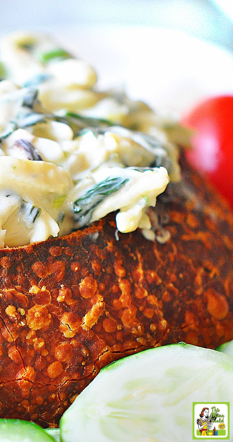 Hot crab and spinach dip served in a bread bowl with vegetables.