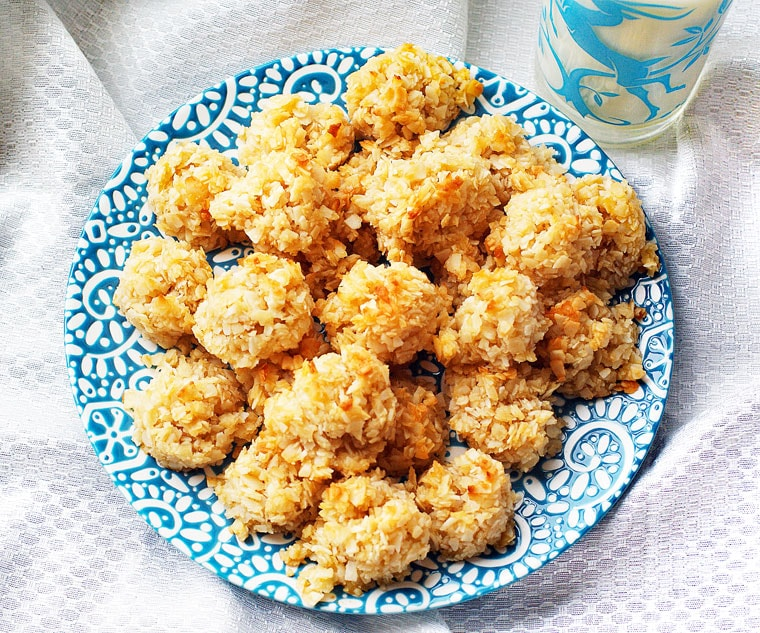 An overhead shot of a white and blue plate of golden coconut macaroons with a blue glass of milk on a white cloth.