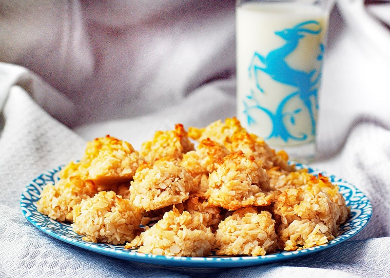 A plate of Coconut Macaroons cookies with a glass of milk.