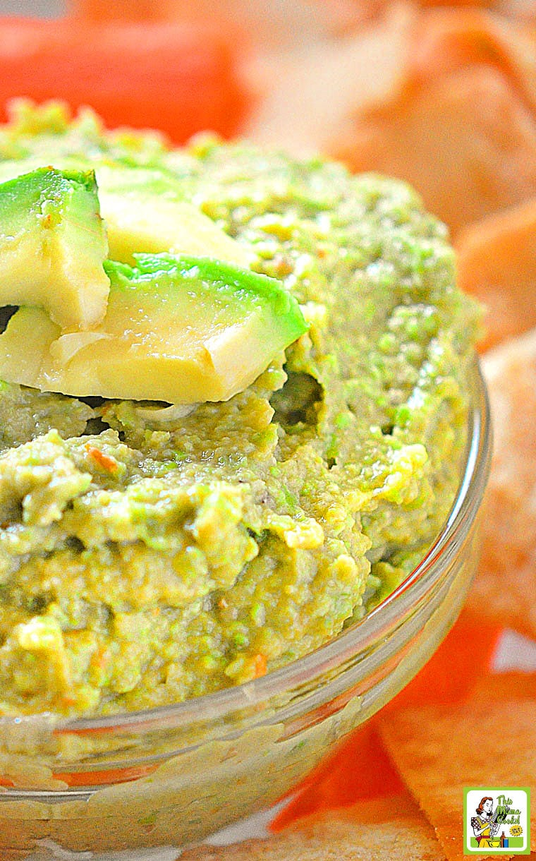 Edamame Avocado Dip in a glass bowl with a slice of avocado.
