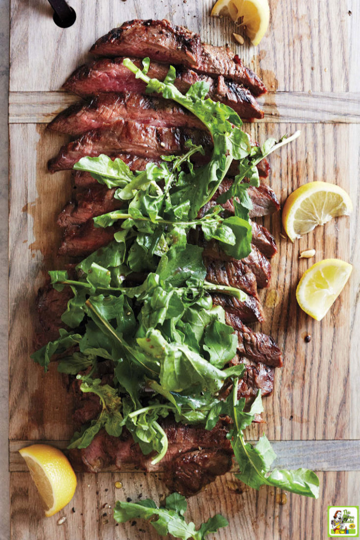 Sliced grillied flank steak with arugula on a wooden with lemon slices.