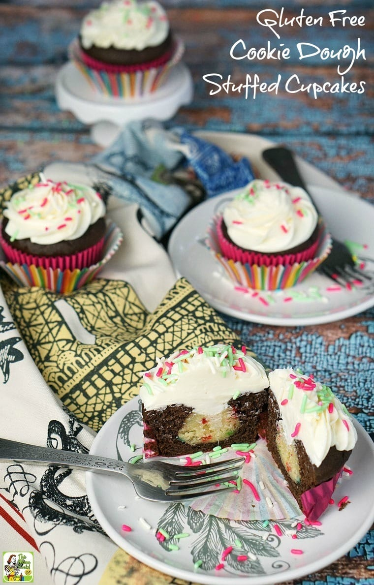 Cookie Dough Stuffed Cupcake on a plates, kitchen towels, and mini cake stands.