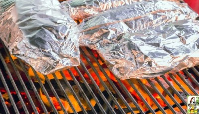 Grilled salmon in foil over a campfire