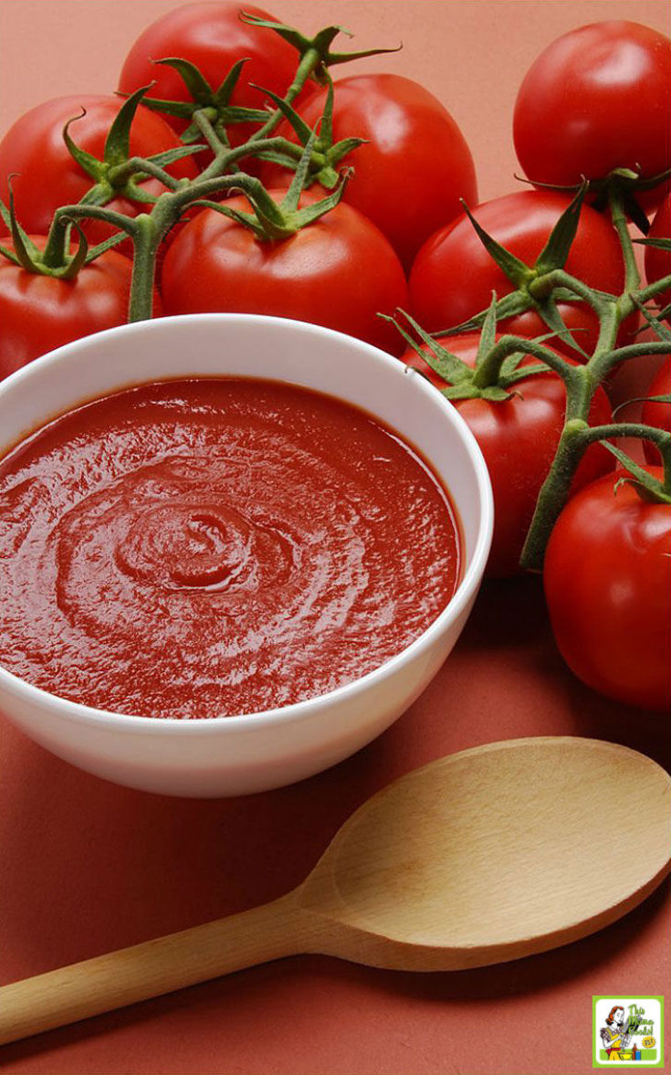 A bowl of freshly made tomato sauce, a wooden spoon, and tomatoes on the vine.