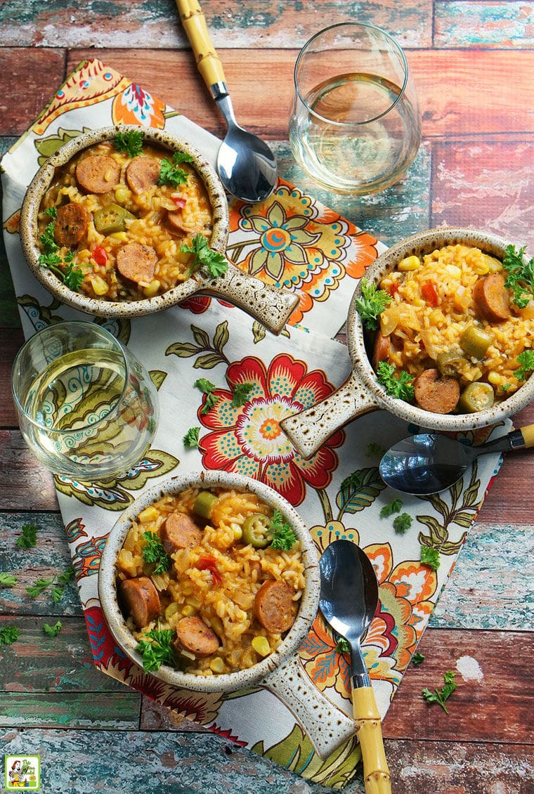 Overhead shot of three bowls of Andouille Sausage Jambalaya on a colorful floral napkin. with a glass of white white and soup spoons.