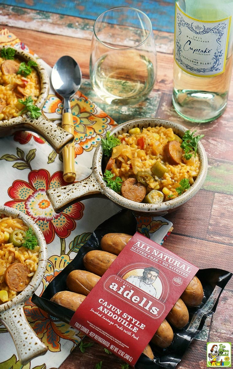 Bowls of jambalaya, a package of Aidells Aindouille sausage, a wine glass, a bottle of wine, and spoons on a colorful napkin.