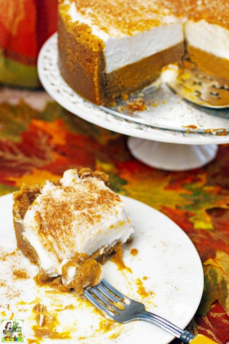 Slice of a gluten free dairy free pumpkin pie on a white plate. Deep dish pumpkin pie on a white pie stand.