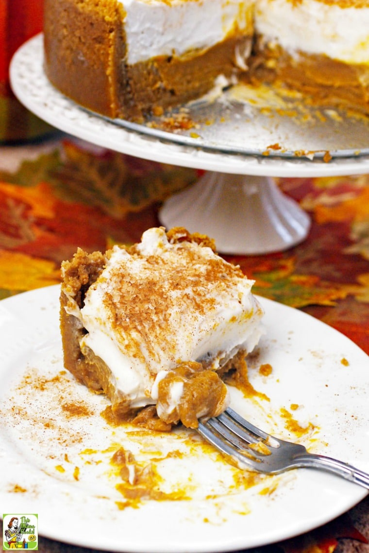 Eaten slice of gluten free dairy free pumpkin pie on a white plate. Deep dish pumpkin pie with slice removed on a white cake stand.