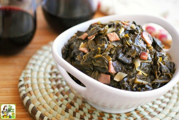 A white bowl of easy sweet collard greens on a woven mat with red wine glasses in the background.