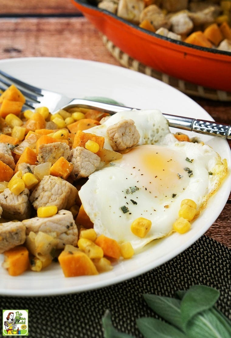 A plate of Sweet Potato Pork Hash with sunny side up eggs, and a fork with a skillet of pork hash in the background