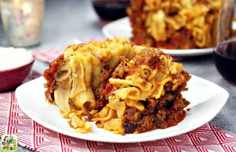 A plate of slow cooker baked ziti on a napkin with a wine glass and bowl of grated cheese.