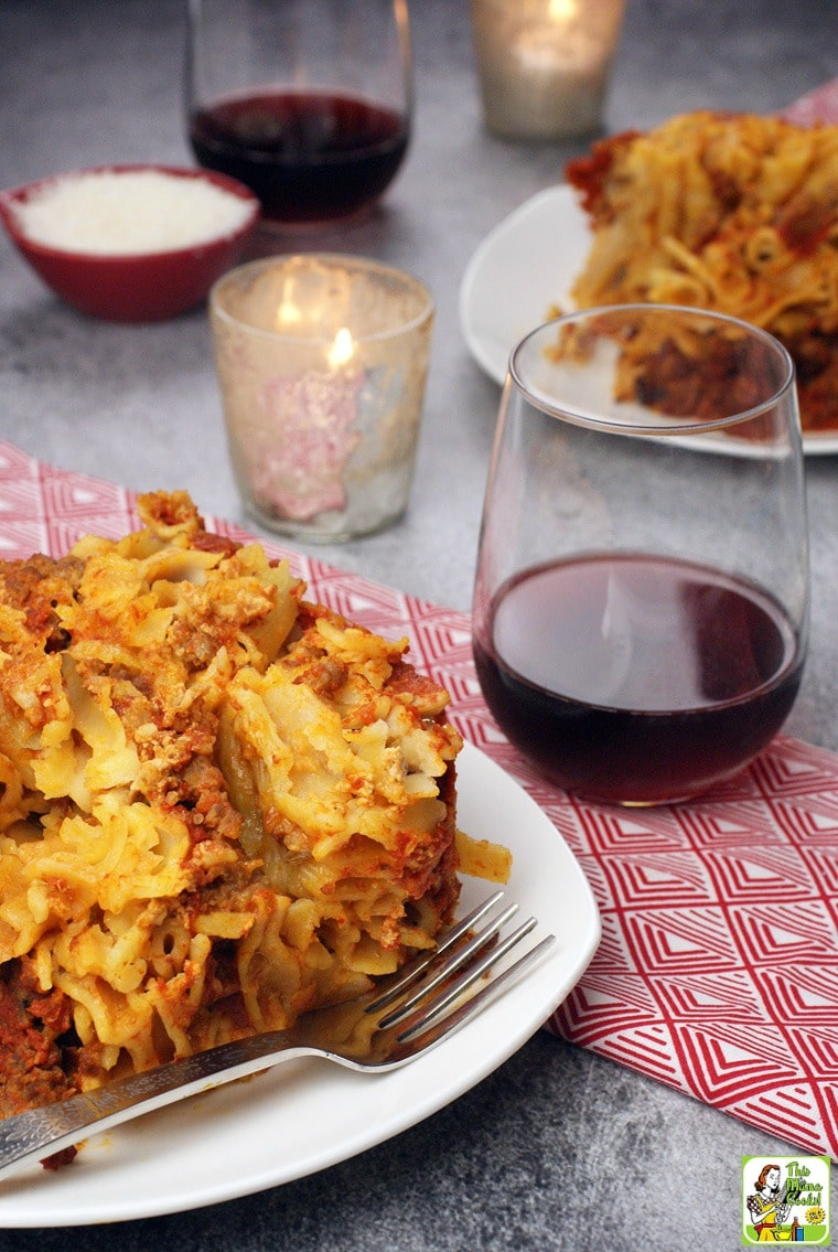 A plate of slow cooker baked ziti on a white plate with silver fork with a red napkin with a glass of red wine with a candle, another plate of ziti, and a small bowl of shredded cheese.