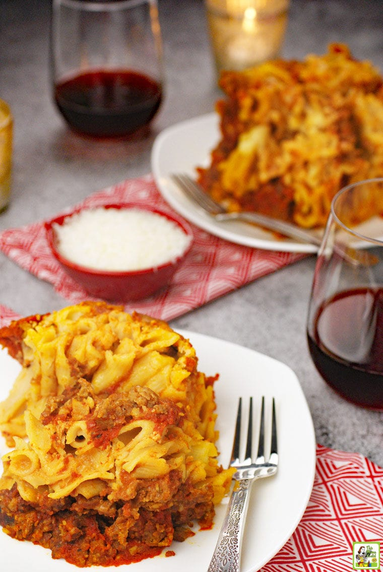 Plates of slow cooker baked ziti on white plates with forks, red napkins, a small red bowl of shredded cheese, and glasses of red wine.