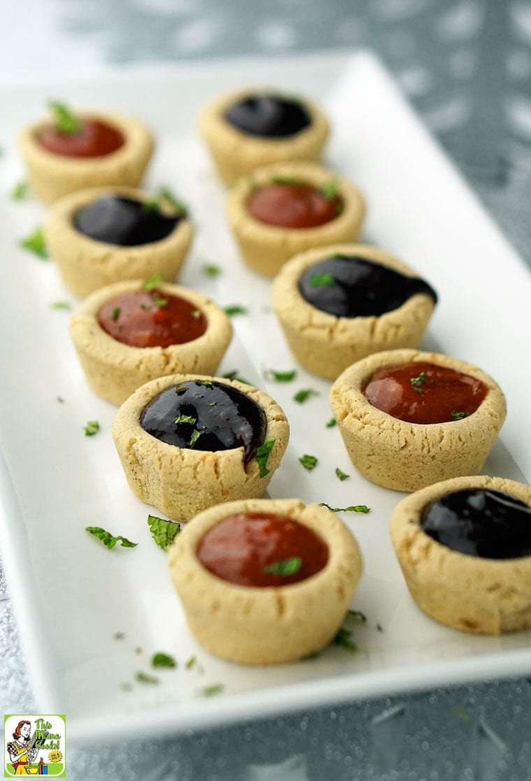 A long rectangular white plate of purple and orange Fruit Filled Cookie Cups with mint garnish on a silver background.