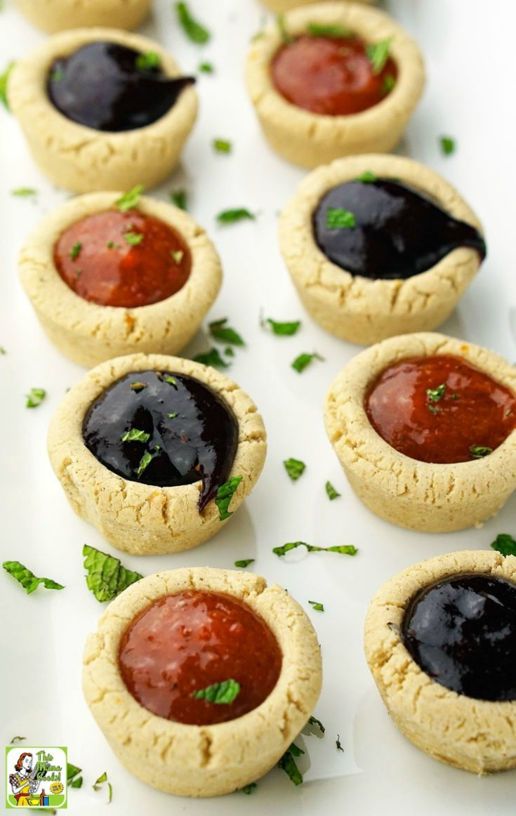 A long white tray of cherry and peach fruit filled cookie cups.