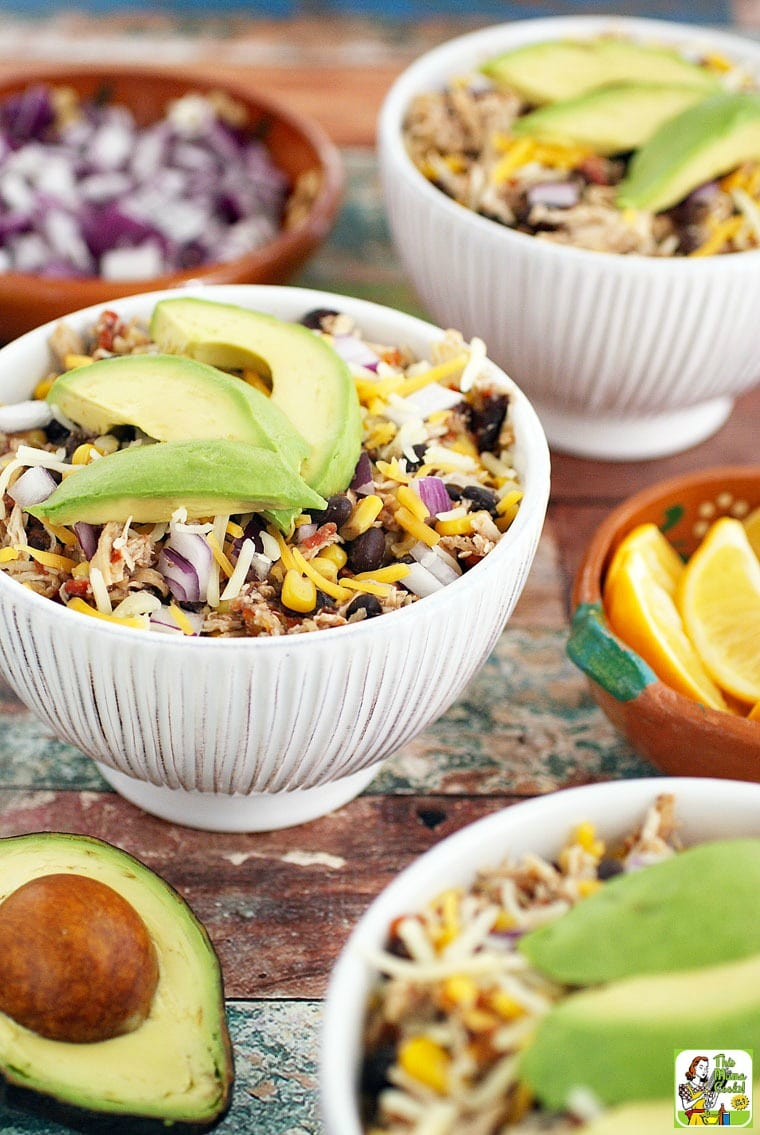White Bowls of Mexican Shredded Chicken with beans, cheese, onions, and avocados