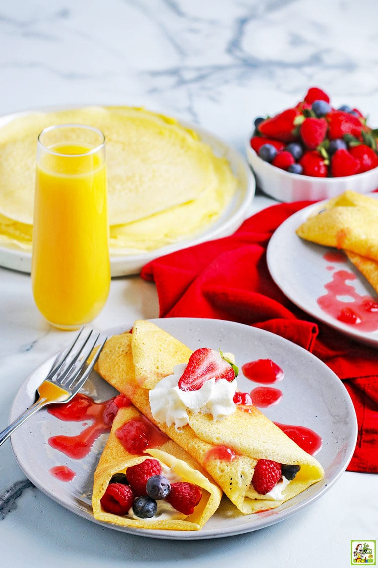 A plate of rice flour crepes with raspberries, blueberries, whipped cream, and berry drizzle with red napkins and a glass of orange juice.
