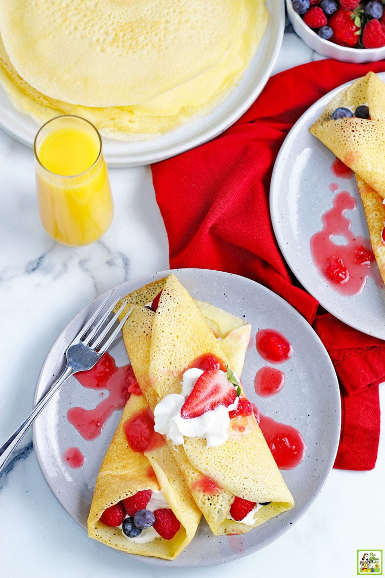Overhead shot of two gluten free crepes stuffed with berries and covered in whipped cream and strawberry drizzle with napkins, and other plates of crepes, and a glass of orange juice.