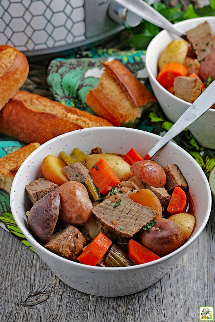 Closeup of a bowl of crockpot venison stew with pieces of French bread in the background.