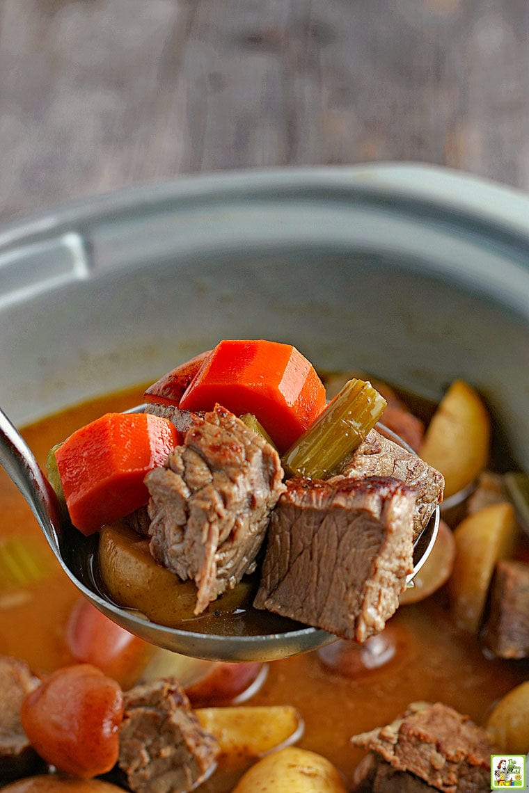 Closeup of a spoonful of venison and vegetable stew above a crockpot of stew.