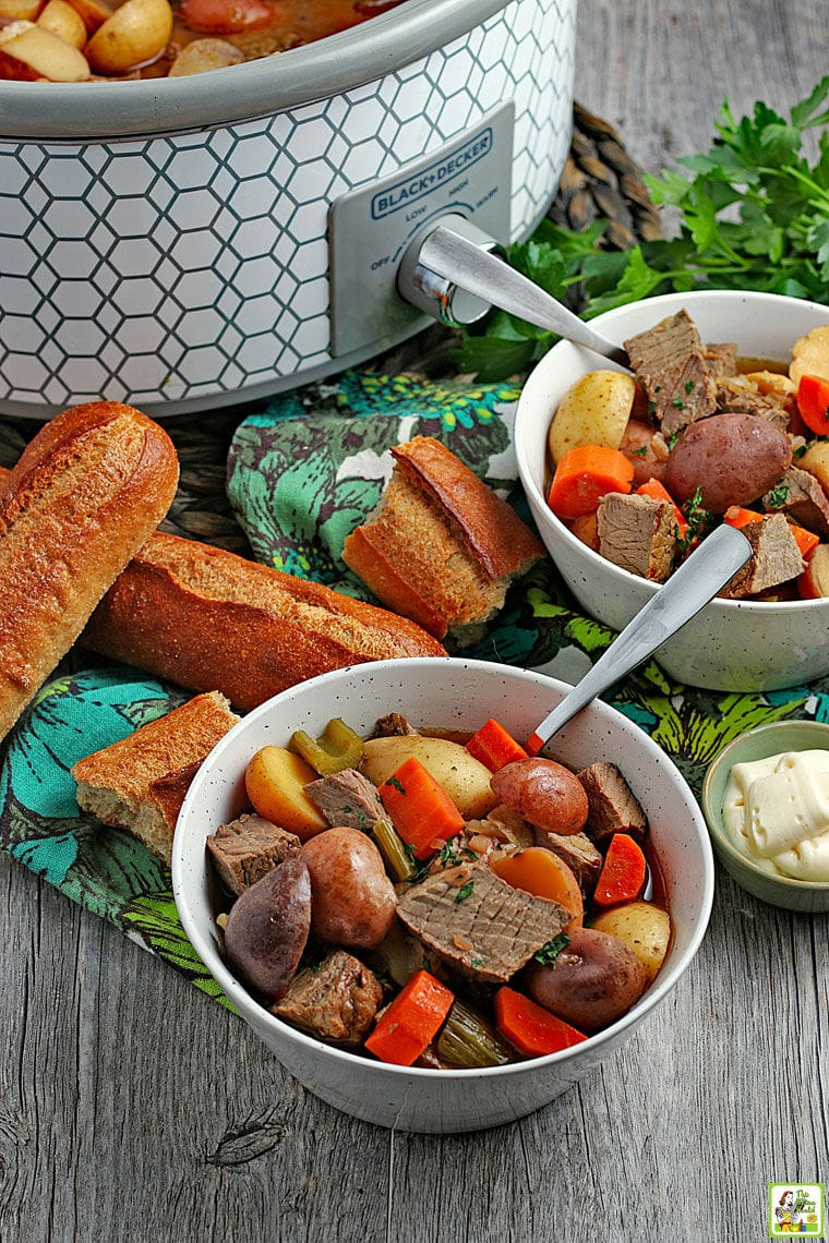 White ceramic bowls of venison and vegetable stew with spoons, colorful napkins, bread rolls, a small bowl of horseradish, and a slow cooker in the background.