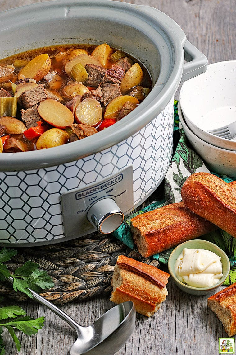 A slow cooker of venison stew with vegetables and potatoes with a ladle, chunks of bread, a bowl of horseradish, and plates in the foreground.