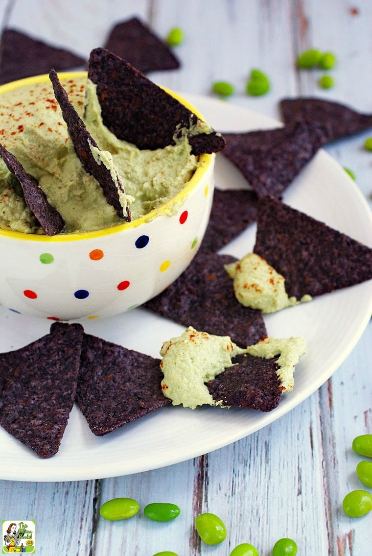 A white bowl with polka dots with blue tortilla chips dipped into green edamame hummus. Placed on a white plate.