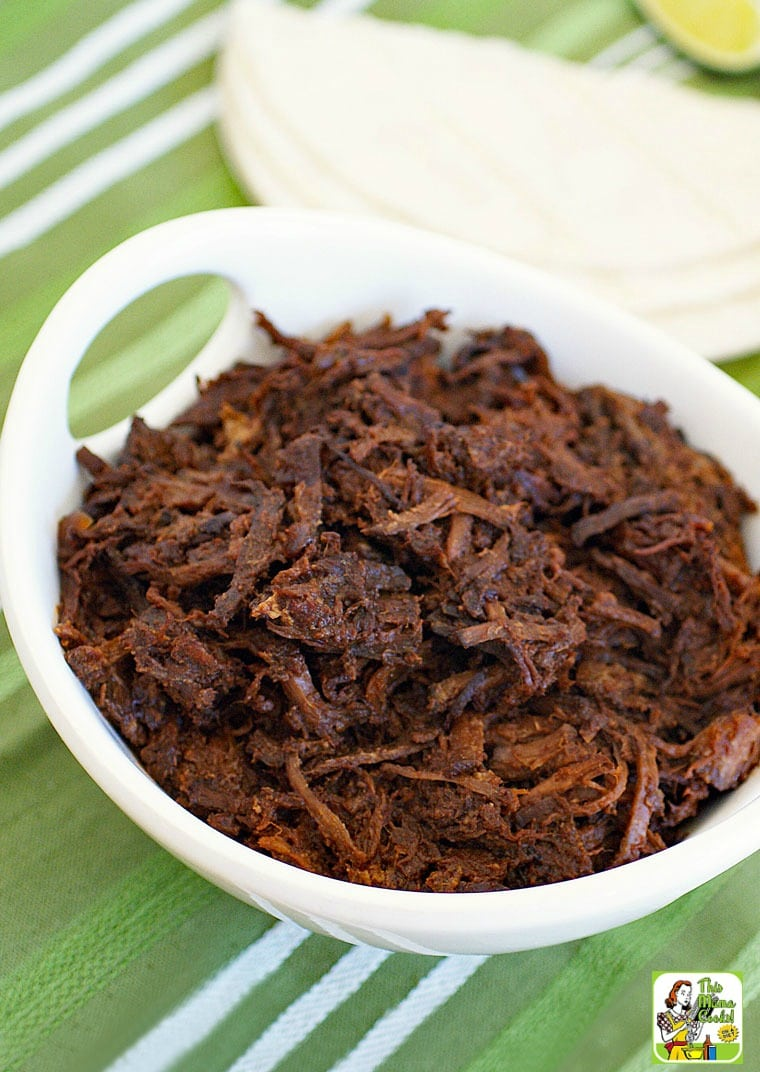 A bowl of shredded slow cooker goat with tortillas in the background.