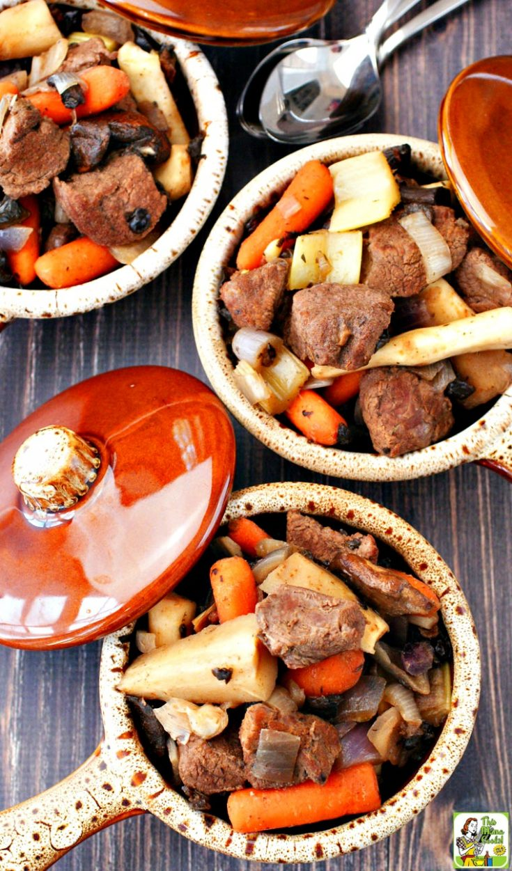 Closeup overhead view of three bowls of venison deer stew filled with root vegetables with lids and spoons.