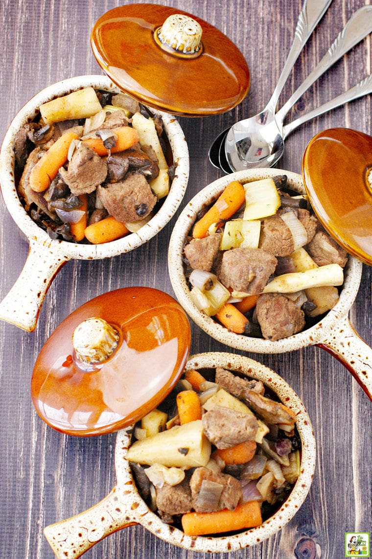 Overhead view of three brown bowls with lids of crockpot deer stew filled with carrots, parsnips, onions, and mushrooms and silver spoons.