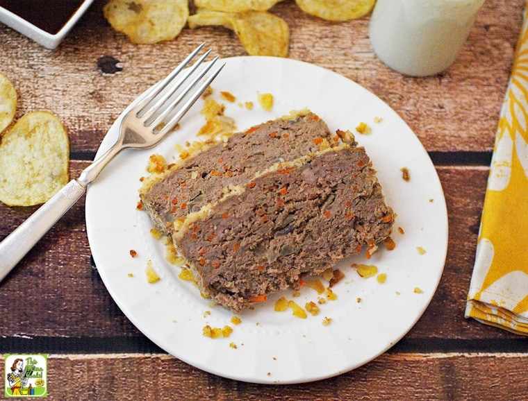A plate of Gluten Free Meatloaf with Potato Chips & Carrots, fork, glass of milk, yellow napkin, potato chips, and dish of BBQ sauce.